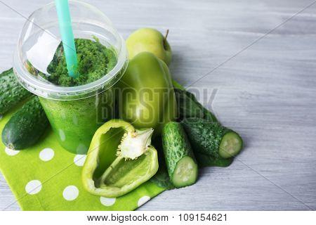 Fresh vegetable juice on color wooden background
