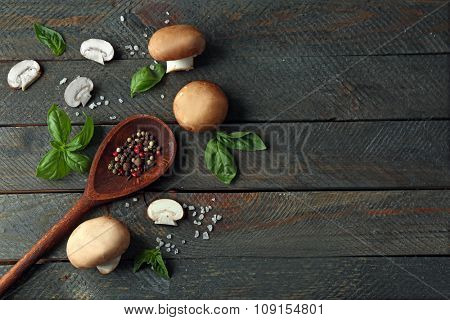 Fresh mushrooms, basil leaves and spices on wooden background