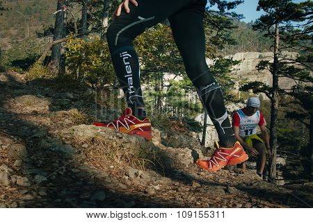 closeup feet of male runner running uphill on a mountain trail