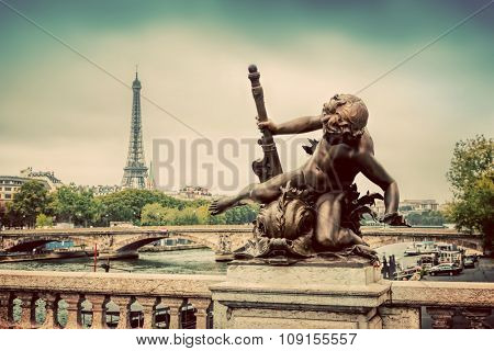 Artistic statue on Pont Alexandre III bridge in Paris, France. Seine river and Eiffel Tower. Vintage