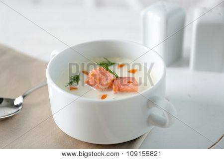 Delicious salmon cream soup on white served table in the restaurant