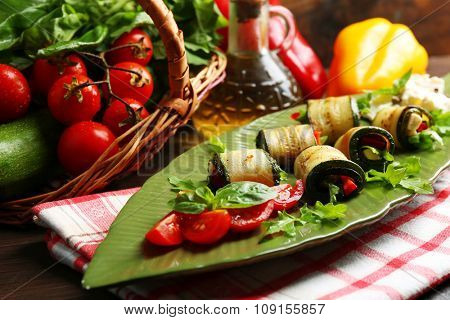 Zucchini rolls with cheese, bell peppers and arugula on plate, close-up, on table background