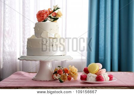 Beautiful wedding cake decorated with flowers on pink table in the room