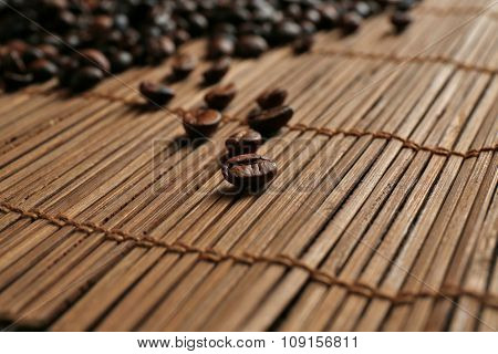 Aromatic coffee beans scattered on bamboo mat