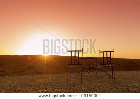 Table and two chairs in the desert facing the sunset
