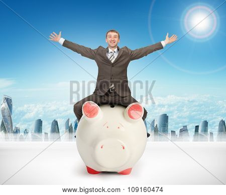 Happy businessman sitting on piggy bank