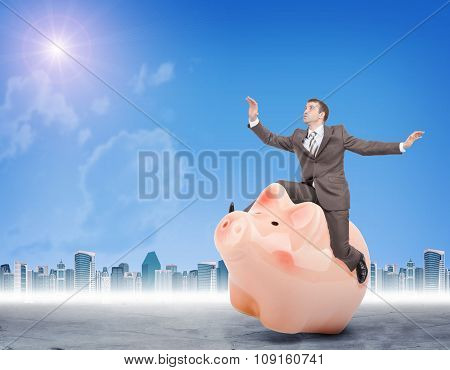 Man in suit sitting on piggy bank
