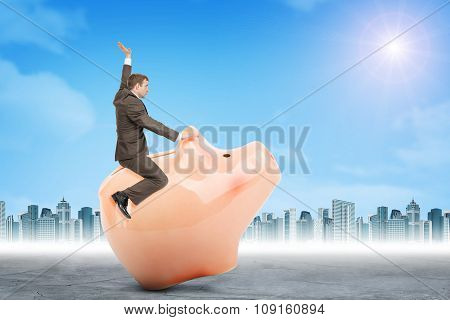 Businessman sitting on piggy bank, side view