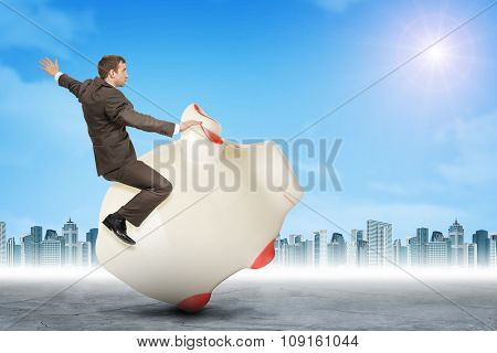 Man sitting on white piggy bank