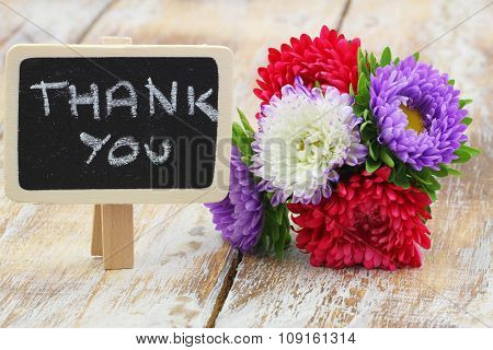 Thank you written on little blackboard with colorful aster flower bouquet