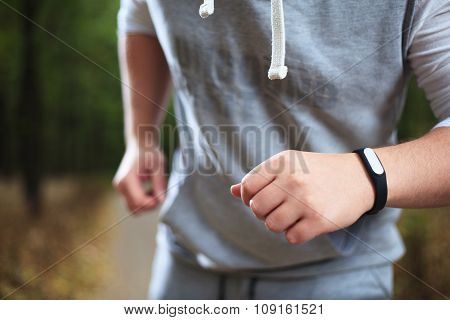 Young Man Using Fitness Bracelet During Morning Run