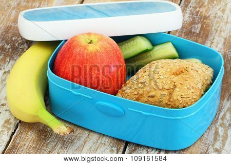 Healthy lunch box consisting mixed grain cheese roll, red apple, cucumber sticks and banana