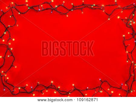 Christmas lights of different colors frame on red background