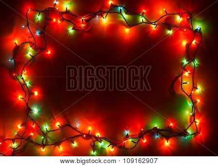 Christmas lights of different colors frame on wooden planks
