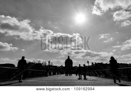 Silhouette of people walking on Pont des Arts in Paris, France. Black and white photograph.