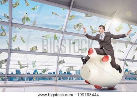 Businessman sitting on white piggy bank in office