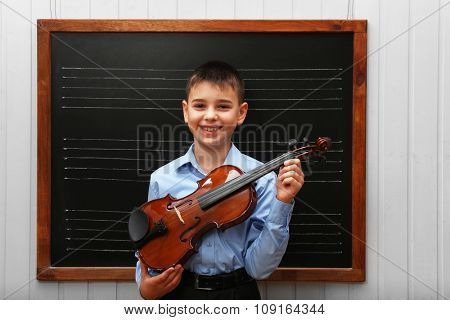 Young cute schoolboy holding the violin at the blackboard