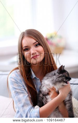 Beautiful young woman with cat at home