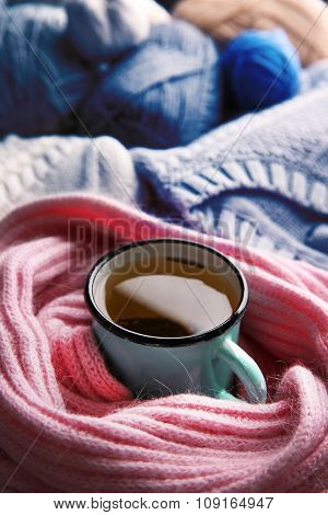 Mug of tea wrapped in scarf and warm clothes beside it closeup