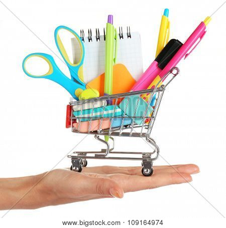 Bright stationery objects in mini supermarket cart on hand isolated on white background
