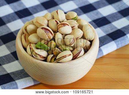 Pistachio nuts in wooden bowl on navy blue and white cloth