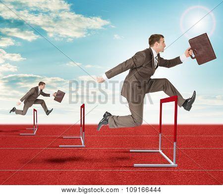 Businessmen hopping over treadmill barrier