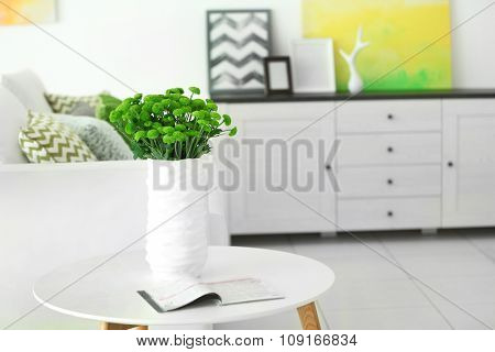 Beautiful green chrysanthemums in vase on table in room