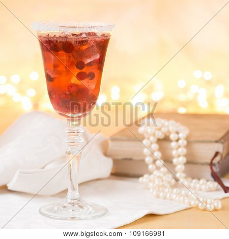 Glass Of Champagne And Cranberry Cocktail With Vintage Books And Pearls, With Bokeh Lights