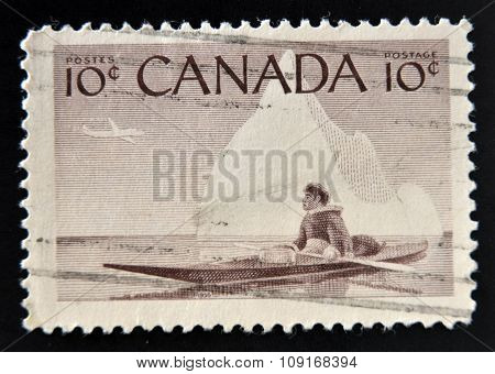 CANADA - CIRCA 1955: stamp printed in Canada shows Eskimo on a kayak against the background