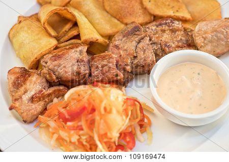 Grilled pork, baked potatoes and vegetable salad