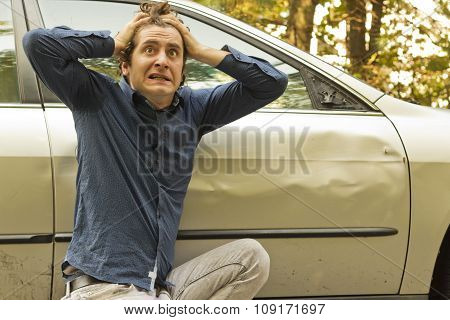 Silly man makes angry annoyed facial expression about dame to his car
