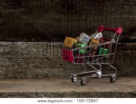 trolley cart with gift boxes over wooden background
