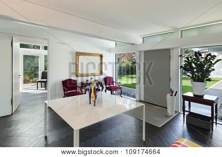 Architecture, open space of a modern house, room with table and artwork