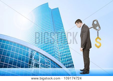 Businessman with key in back and cityscape