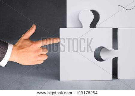 Businessman hand pushing puzzle piece