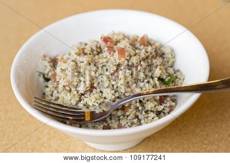 Bowl of fresh organic quinoa salad in large white bowl