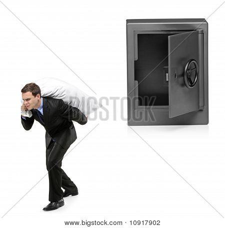Full Length Portrait Of A Man Stealing A Money Bag From A Deposit Safe
