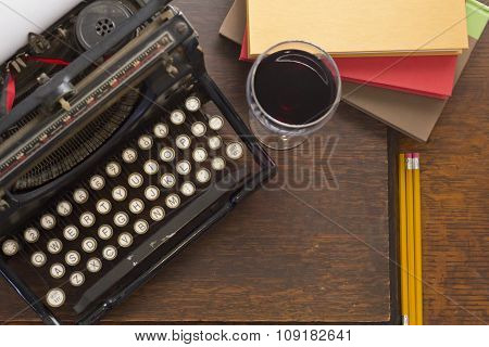 Old vintage typewriter with glass of wine pencils and books in this retro creative writing and relazation themed desk top