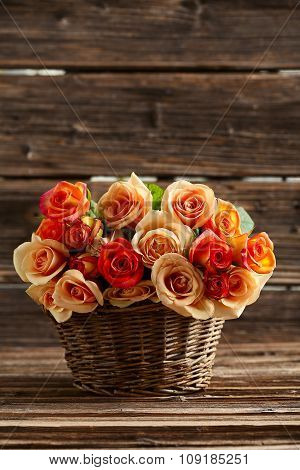 Bouquet Of Orange Roses In Basket On Brown Wooden Background