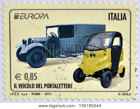 Stamp printed in Italy shows an old post car and a contemporary hybrid driven vehicle