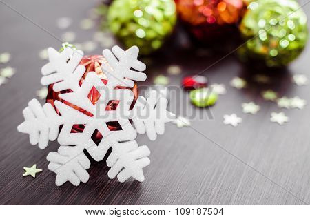 White Snowflake On Background Of Red And Green Xmas Baubles.