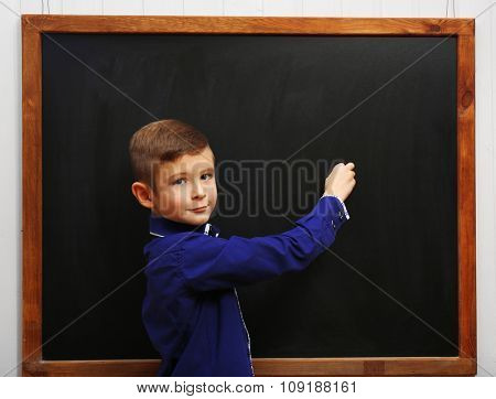 Cute boy posing at the clean blackboard, in the classroom