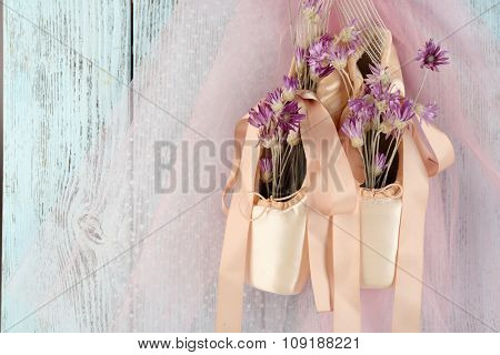 Decorated ballet shoes with flowers in it hanging on blue wooden background