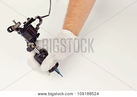 Tattoo machine in male's hand isolated on white background