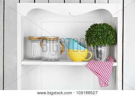Clean glasses, plates and cutlery on shelf in kitchen cupboard