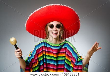 Girl in mexican vivid poncho with maracas against gray