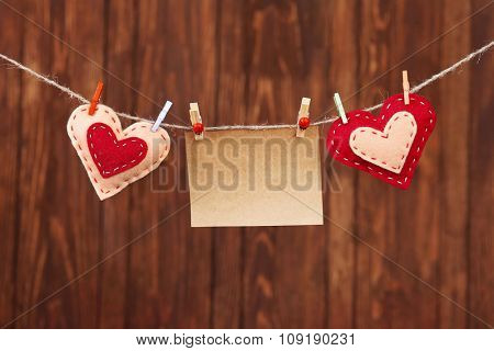 Red hearts and blank note, on wooden background