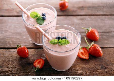 Fresh strawberry yogurt with berries around on wooden background