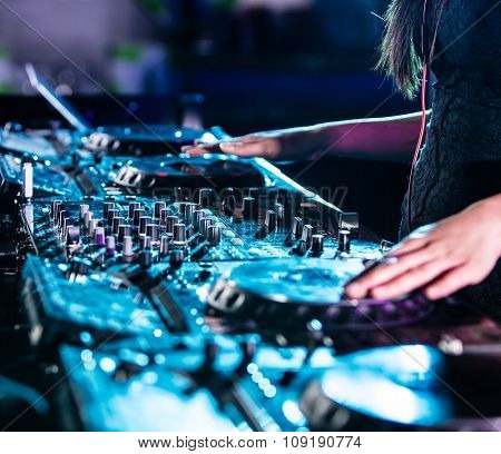 Dj mixes the track in the nightclub.