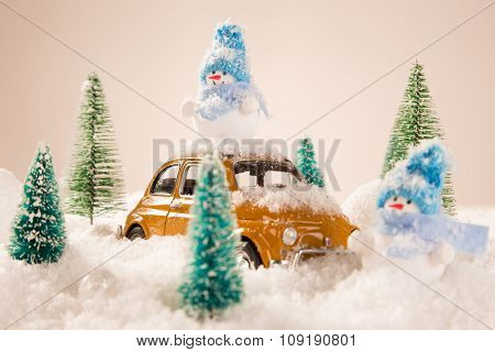 Miniature yellow car with spruce trees